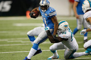 Reggie Bush #21 of the Detroit Lions tries to avoid the tackle by Dion Jordan #95 of the Miami Dolphins in the third quarter at Ford Field on November 09, 2014 in Detroit, Michigan.