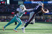 Rob Gronkowski #87 of the New England Patriots catches a touchdown pass as he is defended by Reshad Jones #20 of the Miami Dolphins during the first quarter of a game at Gillette Stadium on November 26, 2017 in Foxboro, Massachusetts.