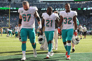 Center Daniel Kilgore #67, running back Frank Gore #21 and running back Kenyan Drake #32 of the Miami Dolphins walk off field after their 20-12 win over the New York Jets at MetLife Stadium on September 16, 2018 in East Rutherford, New Jersey.