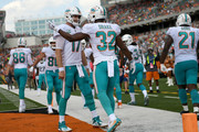 Kenyan Drake #32 of the Miami Dolphins is congratulated by Ryan Tannehill #17 after scoring a touchdown during the second quarter of the game against the Cincinnati Bengals  at Paul Brown Stadium on October 7, 2018 in Cincinnati, Ohio.