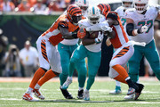 Preston Brown #52 of the Cincinnati Bengals and Carlos Dunlap #96 combine to tackle Kenyan Drake #32 of the Miami Dolphins during the first quarter at Paul Brown Stadium on October 7, 2018 in Cincinnati, Ohio.