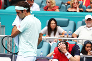 John Isner sits after a leg injury against Roger Federer of Switzerland during the Men's Final match on day 14 of the Miami Open presented by Itau at Hard Rock Stadium on March 31, 2019 in Miami Gardens, Florida.