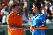 Novak Djokovic of Serbia holds the Butch Bucholz trophy as he shakes hands with the 1985 winner Tim Mayotte of the United States after his three set victory against Andy Murray of Great Britain in the mens final during the Miami Open Presented by Itau at Crandon Park Tennis Center on April 5, 2015 in Key Biscayne, Florida.