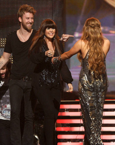 Miley Cyrus Singer Miley Cyrus (R) presents musician Charles Kelley and singer Hillary Scott of Lady Antebellum the Country Album Award onstage during The 53rd Annual GRAMMY Awards held at Staples Center on February 13, 2011 in Los Angeles, California.