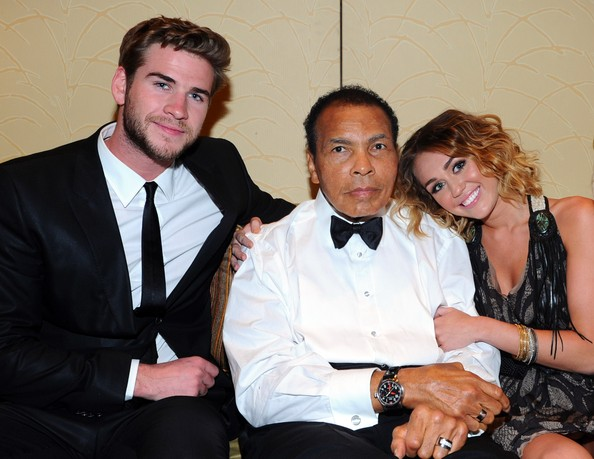 Miley Cyrus Actor Liam Hemsworth, Muhammad Ali, and singer Miley Cyrus pose backstage during Muhammad Ali's Celebrity Fight Night XIII held at JW Marriott Desert Ridge Resort & Spa on March 24, 2012 in Phoenix, Arizona.