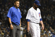 Jon Lester (R) of the Chicago Cubs leaves the game with the trainer against the Milwaukee Brewers during the sixth inning on September 10, 2018 at Wrigley Field  in Chicago, Illinois.