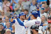 Anthony Rizzo #44 of the Chicago Cubs (R) celebrates with David Bote #13 (L) after hitting a two run home run during the first inning as Manny Pina #9 of the Milwaukee Brewers looks on at Wrigley Field on August 15, 2018 in Chicago, Illinois.