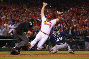 Matt Holliday #7 of the St. Louis Cardinals scores the game-winning run against Jonathan Lucroy #20 of the Milwaukee Brewers in the seventh inning at Busch Stadium on September 17, 2014 in St. Louis, Missouri.  The Cardinals beat the brewers 2-0.