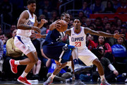 Andrew Wiggins #22 of the Minnesota Timberwolves spins as he is guarded by Tyrone Wallace #12 and Lou Williams #23 of the LA Clippers during a 126-118 Timberwolves win at Staples Center on January 22, 2018 in Los Angeles, California.