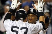 Robinson Cano #24 of the New York Yankees celebrates with teammate Melky Cabrera #53 after scoring a run in the fourth inning against the Minnesota Twins in Game One of the ALDS during the 2009 MLB Playoffs at Yankee Stadium on October 7, 2009 in the Bronx borough of New York City.
