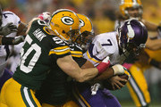 Quarterback  Christian Ponder #7 of the Minnesota Vikings is sacked by  Nick Perry #53 and  A.J. Hawk #50 of the Green Bay Packers in the second quarter of the NFL game at Lambeau Field on October 2, 2014 in Green Bay, Wisconsin.