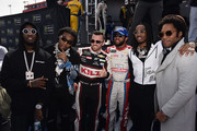 Austin Dillon, driver of the #3 Dow Coating Chevrolet, and Darrell Wallace Jr., driver of the #43 Farmer John Chevrolet, pose for a photo with Migos and Johnathan Fernandez prior to the Monster Energy NASCAR Cup Series Auto Club 400 at Auto Club Speedway on March 18, 2018 in Fontana, California.
