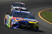 Kyle Busch, driver of the #18 M&M's Caramel Toyota, leads Clint Bowyer, driver of the #14 Haas 30 Years of the VF1 Ford, during the Monster Energy NASCAR Cup Series Gander Outdoors 400 at Pocono Raceway on July 29, 2018 in Long Pond, Pennsylvania.
