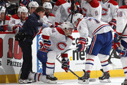 Head athletic trainer Graham Rynbend helps Alexei Emelin #74 of the Montreal Canadiens after he was injured on a play as team mate Andrei Markov #79  looks on during an NHL game at Canadian Tire Centre on January 16, 2014 in Ottawa, Ontario, Canada.