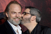"Hugo Weaving receives a kiss from director Christian Rivers as they attend the ""Mortal Engines"" world premiere at Cineworld Leicester Square on November 27, 2018 in London, England."