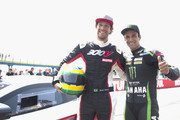 """Johann Zarco of France and Monster Yamaha Tech 3 and Bruno Senna . of Brasile (L) pose during the pre-event """"A race between a Yamaha M1 and a McLaren GT3"""" during the MotoGP Netherlands - Preview on June 22, 2017 in Assen, Netherlands."""