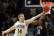 Scott Martin #14 of the Notre Dame Fighting Irish passes against Brett McKnight #23 of the Akron Zips in the second half during the second round of the 2011 NCAA men's basketball tournament at the United Center on March 18, 2011 in Chicago, Illinois.