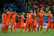 (L-R) Daley Blind, Stefan de Vrij, Klaas-Jan Huntelaar, Wesley Sneijder, Dirk Kuyt, Jeremain Lens, Georginio Wijnaldum and Ron Vlaar of the Netherlands congratulate Arjen Robben on his made penalty kick in a shootout during the 2014 FIFA World Cup Brazil Quarter Final match between the Netherlands and Costa Rica at Arena Fonte Nova on July 5, 2014 in Salvador, Brazil.