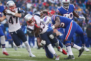 Dion Lewis #33 of the New England Patriots runs the ball as Kyle Williams #95 of the Buffalo Bills and Jerry Hughes #55 of the Buffalo Bills attempt to tackle him December 3, 2017 at New Era Field in Orchard Park, New York.