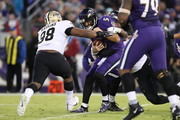 Quarterback Joe Flacco #5 of the Baltimore Ravens is sacked by defensive end Alex Okafor #57 of the New Orleans Saints in the fourth quarter at M&T Bank Stadium on October 21, 2018 in Baltimore, Maryland.