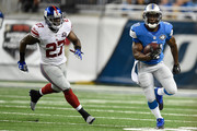 Reggie Bush #21 of the Detroit Lions rushes, pursued by Stevie Brown #27 of the New York Giants in the first quarter during a game at Ford Field on September 8, 2014 in Detroit, Michigan.