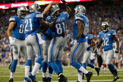 Calvin Johnson #81 of the Detroit Lions celebrates a first quarter touchdown with Reggie Bush #21 and Eric Ebron #85 while playing the New York Giants at Ford Field on September 8, 2014 in Detroit, Michigan.
