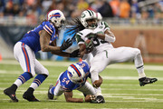Chris Ivory #33 of the New York Jets is tackled by Larry Dean #54 and Brandon Spikes #51 of the Buffalo Bills in the fourth quarter at Ford Field on November 24, 2014 in Detroit, Michigan.