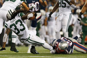 Chris Ivory #33 of the New York Jets is tackled by Patrick Chung #23 of the New England Patriots during the first quarter at Gillette Stadium on October 16, 2014 in Foxboro, Massachusetts.