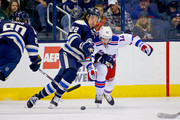 Sonny Milano #22 of the Columbus Blue Jackets battles for control of the puck with Eric Staal #12 of the New York Rangers during the first period on April 4, 2016 at Nationwide Arena in Columbus, Ohio.