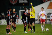 Andy Najar #14 of D.C. United is shown a second yellow card by referee Jair Marrufo in the second half against the New York Red Bulls during their Eastern Conference Semifinal match at RFK Stadium on November 3, 2012 in Washington, DC.