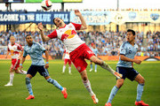 Sacha Kljestan #16 of New York Red Bulls competes for the ball as Amadou Dia #13 and Roger Espinoza #27 of Sporting KC look on during the game at Sporting Park on March 8, 2015 in Kansas City, Kansas.