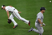 First baseman Chris Davis #19 of the Baltimore Orioles errors as he flips the ball behind his back attempting to get Matt Holliday #17 of the New York Yankees out at first base during the eighth inning at Oriole Park at Camden Yards on May 30, 2017 in Baltimore, Maryland.