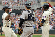 John Ryan Murphy #66 of the New York Yankees looks on as Aaron Hicks #32 of the Minnesota Twins congratulates Torii Hunter #48 (L) on a three-run home run during the third inning of the game on July 25, 2015 at Target Field in Minneapolis, Minnesota.