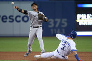 Starlin Castro #14 of the New York Yankees turns a double play in the fifth inning during MLB game action as Troy Tulowitzki #2 of the Toronto Blue Jays slides into second base at Rogers Centre on June 2, 2017 in Toronto, Canada.
