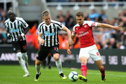 Aaron Ramsey of Arsenal is challenged by Matt Ritchie of Newcastle United during the Premier League match between Newcastle United and Arsenal FC at St. James Park on September 15, 2018 in Newcastle upon Tyne, United Kingdom.