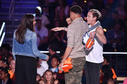 NBA player Stephen Curry (C) accepts the Sickest Moves award from U.S. Women's Soccer players Alex Morgan (L) and Abby Wambach (R) onstage at the Nickelodeon Kids' Choice Sports Awards 2015 at UCLA's Pauley Pavilion on July 16, 2015 in Westwood, California.