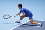 Novak Djokovic of Serbia reaches for a forehand after being lobbed during his singles semi final match against Dominic Thiem of Austria during day seven of the Nitto ATP World Tour Finals at The O2 Arena on November 21, 2020 in London, England.