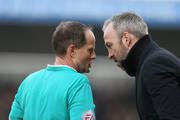 Referee Rob Lewis makes a point to Cambridge United manager Shaun Derry during the Sky Bet League Two match between Northampton Town and Cambridge United at Sixfields Stadium on March 12, 2016 in Northampton, England.