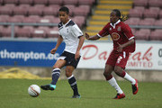 Jake Nicholson of Tottenham Hotspur plays the ball watched by Paul Rodgers of Northampton Town during a Behind Closed Doors Friendly Match between Northampton Town and Tottenham Hotspur at Sixfields Stadium on October 19, 2010 in Northampton, England.