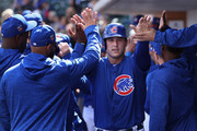 Anthony Rizzo #44 of the Chicago Cubs high fives teammates in the dugout after scoring a run against the Oakland Athletics during the first inning of the spring training game at Sloan Park on February 28, 2018 in Mesa, Arizona.