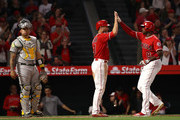 Justin Upton #8 and Zack Cozart #7 of the Los Angeles Angels of Anaheim high five at homeplate after Upton's two-run homerun as catcher Bruce Maxwell #13 of the Oakland Athletics looks on during the fourth inning MLB game at Angel Stadium on April 7, 2018 in Anaheim, California.