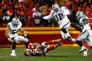 Tyvon Branch #27 of the Kansas City Chiefs recovers an on-side kick as kicker Sebastian Janikowski #11 of the Oakland Raiders leaps to avoid him at Arrowhead Stadium during the fourth quarter of the game on January 3, 2016 in Kansas City, Missouri.