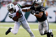 Chris Ivory #33 of the New York Jets stiffarms  Tyvon Branch #33 of the Oakland Raiders during the second quarter at MetLife Stadium on September 7, 2014 in East Rutherford, New Jersey.