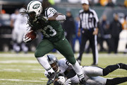 Chris Ivory #33 of the New York Jets runs from Charles Woodson #24 of the Oakland Raiders during their game at MetLife Stadium on December 8, 2013 in East Rutherford, New Jersey.
