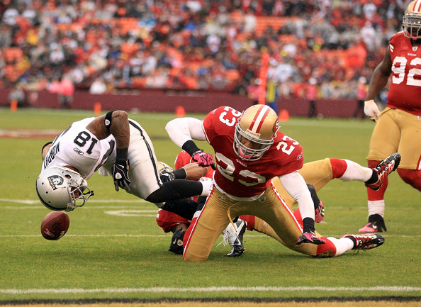 Louis Murphy #18 of the Oakland Raiders fumbles the ball when he was hit by Taylor Mays #23 of the San Francisco 49ers at Candlestick Park on October 17, 2010 in San Francisco, California. Murphy recovered his own fumble on the play.