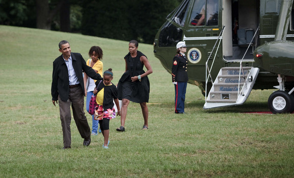 President Barack Obama (L) and First Lady Michelle Obama (R) walk with their daughters Malia (2L) and Sasha (2R) from Marine One on the South Lawn of the White House August 30, 2009 in Washington, DC.  President Barack Obama and the first family returned to Washington after spending a week vacation in Massachusetts's Martha's Vineyard.