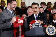 U.S. President Barack Obama (R) receives a football helmet as offenisve line Mike Johnson (2nd L) look on during an East Room event to host members of the Alabama Crimson Tide March 8, 2010 at the White House in Washington, DC. Obama welcomed the 2009 BCS Champions to honor its 13th championship and an undefeated season.