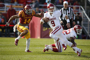 Quarterback Trevor Knight #9 of the Oklahoma Sooners scrambles under pressure from linebacker Jared Brackens #14 of the Iowa State Cyclones in the first half of play at Jack Trice Stadium on November 1, 2014 in Ames, Iowa. The Oklahoma Sooners defeated the Iowa State Cyclones 59-14.