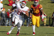 Running back Alex Ross #28 of the Oklahoma Sooners rushes for yards past defensive lineman Vernell Trent #99 of the Iowa State Cyclones in the first half of play at Jack Trice Stadium on November 1, 2014 in Ames, Iowa. The Oklahoma Sooners defeated the Iowa State Cyclones 59-14.