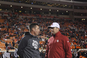 Head Coach Mike Gundy of the Oklahoma State Cowboys and Head Coach Bob Stoops of the Oklahoma Sooners meet before the game November 28, 2015 at Boone Pickens Stadium in Stillwater, Oklahoma.